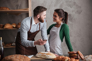 Photo of cheerful loving couple bakers standing near bread and holding mobile phone. Looking aside.