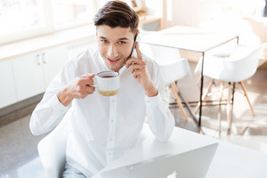 Photo of cheerful man dressed in white shirt using laptop computer while drinking coffee and talking by phone. Coworking. Looking at camera.
