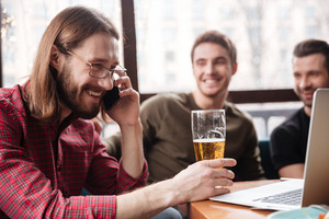 Photo of cheerful men friends sitting in cafe while eating and drinking beer. Talking by phone.
