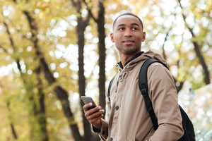 Photo of cheerful young african man holding his phone in hands and looking aside.