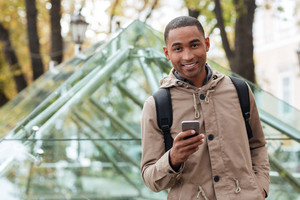 Photo of cheerful young african man holding his phone in hands and looking at camera.