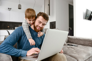 Photo of cheerful young father with cute son using laptop computer indoors. Look at laptop.