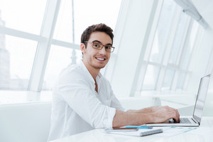 Photo of cheerful young man dressed in white shirt using laptop computer. Look at camera.