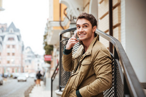 Photo of cheerful young man walking on the street and looking aside while talking by his phone.