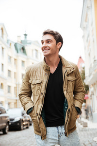 Photo of cheerful young man walking on the street and looking aside.
