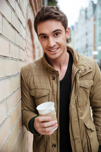 Photo of cheerful young man walking on the street and looking at camera while holding cup of coffee.