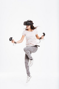 Photo of cheerful young woman wearing virtual reality device holding joysticks and jumping over white background.