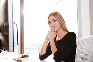 Photo of concentrated happy young lady worker sitting in office near computer. Looking at computer.