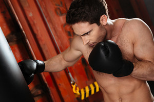 Photo of concentrated strong boxer training in a gym with punchbag. Looking at punchbag.