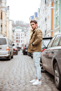Photo of concentrated young man walking on the street and looking at camera.
