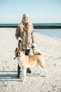 Photo of concentrated young woman walks in winter beach with dog on a leash.