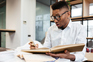 Photo of confused african student wearing eyeglasses in library learning education material with books. Looking at book.