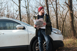 Photo of confused bearded young man wearing hat holding map in the forest standing near car. Looking aside.