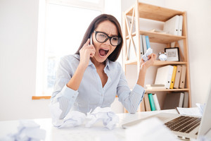 Photo of confused businesswoman dressed in white shirt sitting in her office and screaming while talking by phone