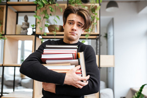Photo of confused caucasian student in library learning education material and holding books in hands. Look at camera.