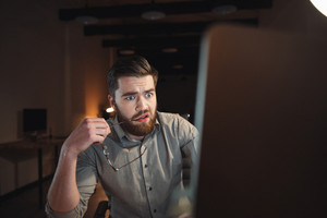 Photo of confused web designer dressed in shirt and holding eyeglasses working late at night and looking at computer.