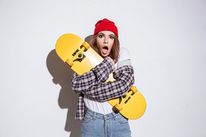 Photo of confused woman dressed in shirt in a cage print wearing hat standing isolated over white background holding skateboard
