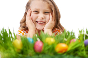 Photo of cute girl lying in green grass with colorful Easter eggs in it