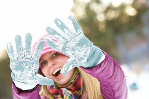 Photo of cute girl showing her gloved hands covered with snow