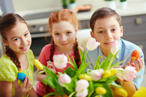 Photo of cute kids with colorful Easter eggs looking at camera