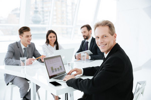 Photo of elderly business man in suit sitting by the table with laptop in office with colleagues