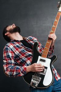Photo of emotional man dressed in shirt in a cage standing over chalkboard while playing on the guitar. Music concept.