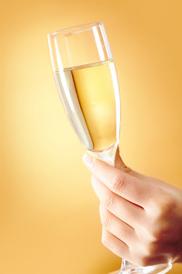 Photo of female hand holding flute of champagne