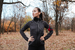 Photo of female runner in warm clothes and headphones looking aside in autumn park