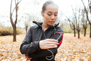 Photo of female runner in warm clothes and headphones looking at phone in autumn park