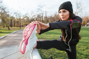 Photo of fitness woman in warm clothes and headphones in autumn park make sport exercise