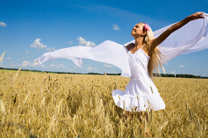 Photo of glad girl holding white chiffon shawl in wheat meadow and looking at sky