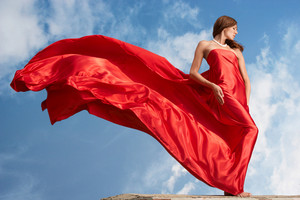 Photo of graceful female folded in bright red silk shawl with cloudy sky at background