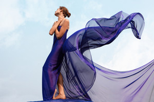 Photo of graceful female folded in dark blue chiffon shawl with cloudy sky at background
