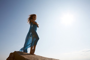 Photo of graceful female folded in dark blue chiffon shawl with sun shining at background
