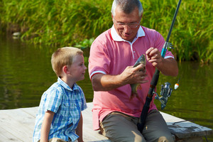 Photo of grandfather and grandson looking at fish caught by them