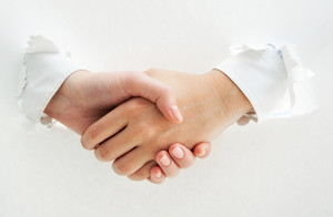 Photo of handshake of business partners through torn paper