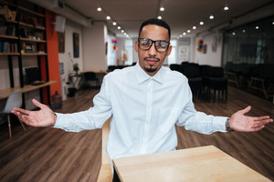 Photo of handsome african businessman wearing glasses sitting at the table and looking at camera. Coworking.