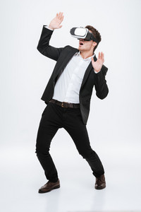 Photo of handsome businessman standing at studio wearing 3d glasses virtual reality. Isolated over white background.