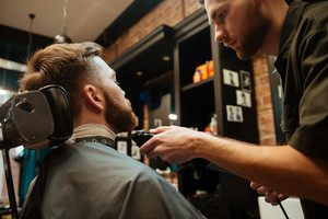 Photo of handsome man getting beard haircut by hairdresser while sitting in chair at barbershop.