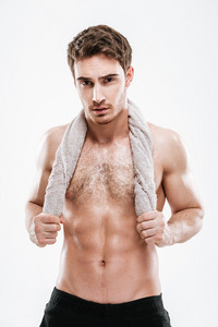 Photo of handsome sportsman standing with towel over white background. Look at camera.