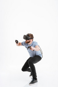 Photo of handsome young bearded man wearing virtual reality device standing over white background.