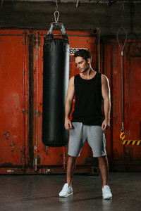 Photo of handsome young strong boxer training in a gym. Looking aside.