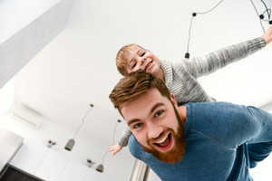 Photo of happy bearded father dressed in blue sweater playing with his little cute son in room indoors