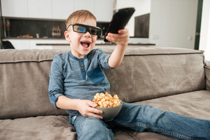 Photo of happy boy on sofa at home watching TV with 3d glasses while eating popcorn. Holding remote control.