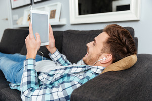 Photo of happy bristle man dressed in shirt in a cage print lies on sofa in home and using tablet computer while listening music with earphones. Looking at white display of tablet computer.