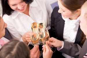 Photo of happy colleagues holding champagne flutes at corporate party