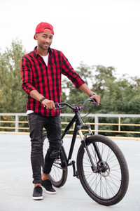 Photo of happy dark skinned guy wearing cap standing near his bicycle. Against nature background. Looking at the camera.