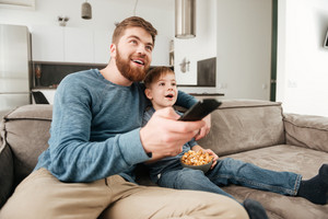 Photo of happy father holding remote control while watching TV with his little cute son holding popcorn.