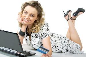 Photo of happy female with card in hand and laptop near by