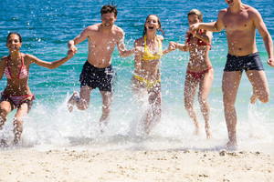 Photo of happy friends splashing water while running out of sea onto shore